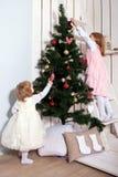 装饰圣诞树的两个小女孩。 免版税库存照片