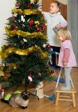 装饰圣诞树的两个小女孩 免版税库存照片