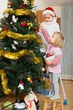 装饰圣诞树的两个小女孩 库存图片
