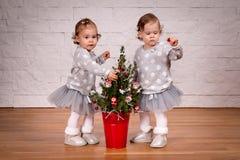 装饰圣诞树的两个小女孩 图库摄影