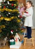 装饰圣诞树的两个小女孩 免版税图库摄影