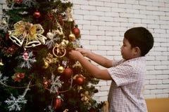 装饰圣诞树的亚洲孩子画象在党面前 图库摄影