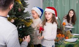 装饰圣诞树的人们 免版税图库摄影