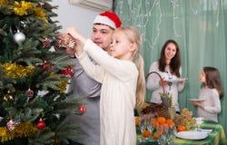 装饰圣诞树的人们 免版税库存图片