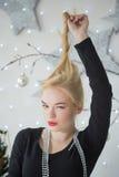 装饰圣诞树的俏丽的妇女 免版税图库摄影