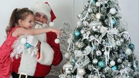 装饰圣诞树的假圣诞老人拿着他的胳膊的一个小女孩 免版税库存图片