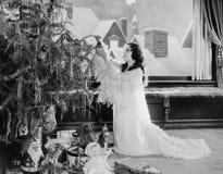 装饰圣诞树的十几岁的女孩(所有人被描述不更长生存,并且庄园不存在 供应商保单那 图库摄影
