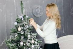 装饰圣诞树的可爱的少妇 免版税库存图片