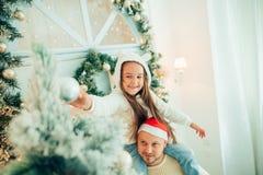 装饰圣诞树的女孩帮助的父亲,拿着一些圣诞节中看不中用的物品 免版税库存图片