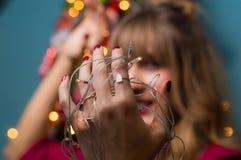 装饰圣诞树的女孩,拿着圣诞灯 免版税图库摄影