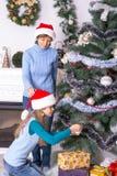 装饰圣诞树的妈妈和女儿 免版税库存图片