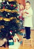 装饰圣诞树的小女孩 免版税图库摄影