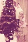 装饰圣诞树的小女孩 图库摄影
