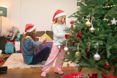 装饰圣诞树的小孩在她的母亲旁边 免版税库存图片