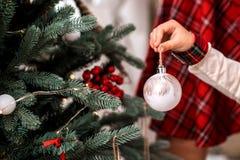 装饰圣诞树的小孩的手户内 免版税图库摄影