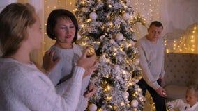 装饰圣诞树的幸福家庭在舒适客厅 球圣诞节查出的心情三白色 股票视频