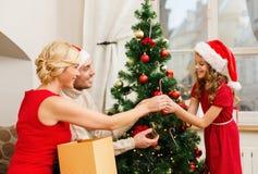 装饰圣诞树的微笑的家庭 图库摄影