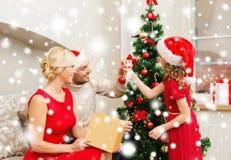 装饰圣诞树的微笑的家庭 免版税库存照片