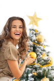 装饰圣诞树的微笑的少妇 库存图片