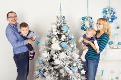 装饰圣诞树的愉快的四口之家人 免版税库存照片
