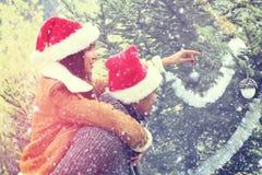 装饰圣诞树的愉快的夫妇室外 免版税库存图片
