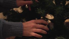 装饰圣诞树的愉快的夫妇的手在屋子里在假日特写镜头前 新年和圣诞节打过工 股票视频