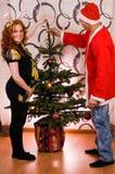 装饰圣诞树的愉快的夫妇 库存图片
