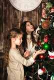 装饰圣诞树的愉快的女孩 免版税库存图片