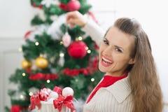 装饰圣诞树的愉快的少妇 免版税库存照片