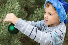 装饰圣诞树的愉快的年轻小男孩 库存图片