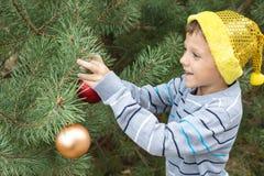 装饰圣诞树的愉快的年轻小男孩 免版税库存图片