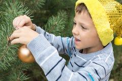 装饰圣诞树的愉快的年轻小男孩 免版税库存照片