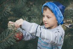 装饰圣诞树的愉快的年轻小男孩 库存照片