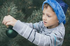 装饰圣诞树的愉快的年轻小男孩 图库摄影