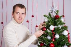 装饰圣诞树的愉快的英俊的人 免版税库存照片
