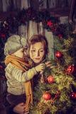 装饰圣诞树的母亲和儿子 图库摄影