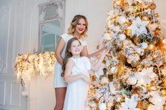 装饰圣诞树的母亲和女儿 库存照片