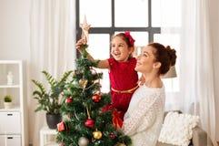 装饰圣诞树的母亲和女儿 免版税库存照片