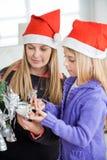 装饰圣诞树的母亲和女儿 免版税库存图片