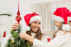 装饰圣诞树的母亲和Dughter 免版税库存照片