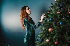 装饰圣诞树的美丽的深色的妇女 免版税库存图片