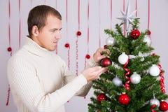 装饰圣诞树的英俊的人画象 免版税库存照片