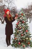 装饰圣诞树的逗人喜爱的少年或女孩室外 免版税库存照片