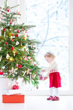 装饰圣诞树的逗人喜爱的矮小的小孩女孩 免版税图库摄影
