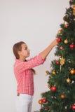 装饰圣诞树的青少年的女孩的明亮的图片 免版税库存图片