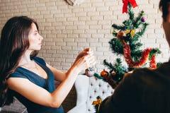 装饰圣诞树的年轻可爱的妇女 库存照片