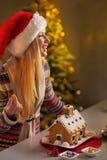 装饰圣诞节曲奇饼房子的少年女孩 免版税库存照片