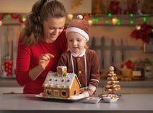 装饰圣诞节曲奇饼房子的母亲和婴孩在厨房里 免版税图库摄影