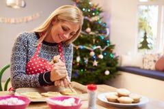 装饰圣诞节曲奇饼的妇女在厨房里 图库摄影