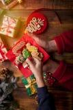 装饰圣诞节曲奇饼的小男孩和妇女的手 免版税库存照片